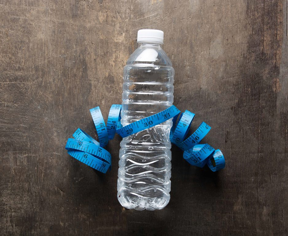 Plastic bottle of water with measuring tape over the wooden background